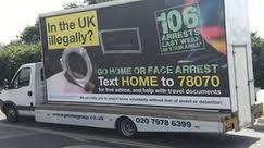 Camiones llevando la gran pancarta sobre la inmigración