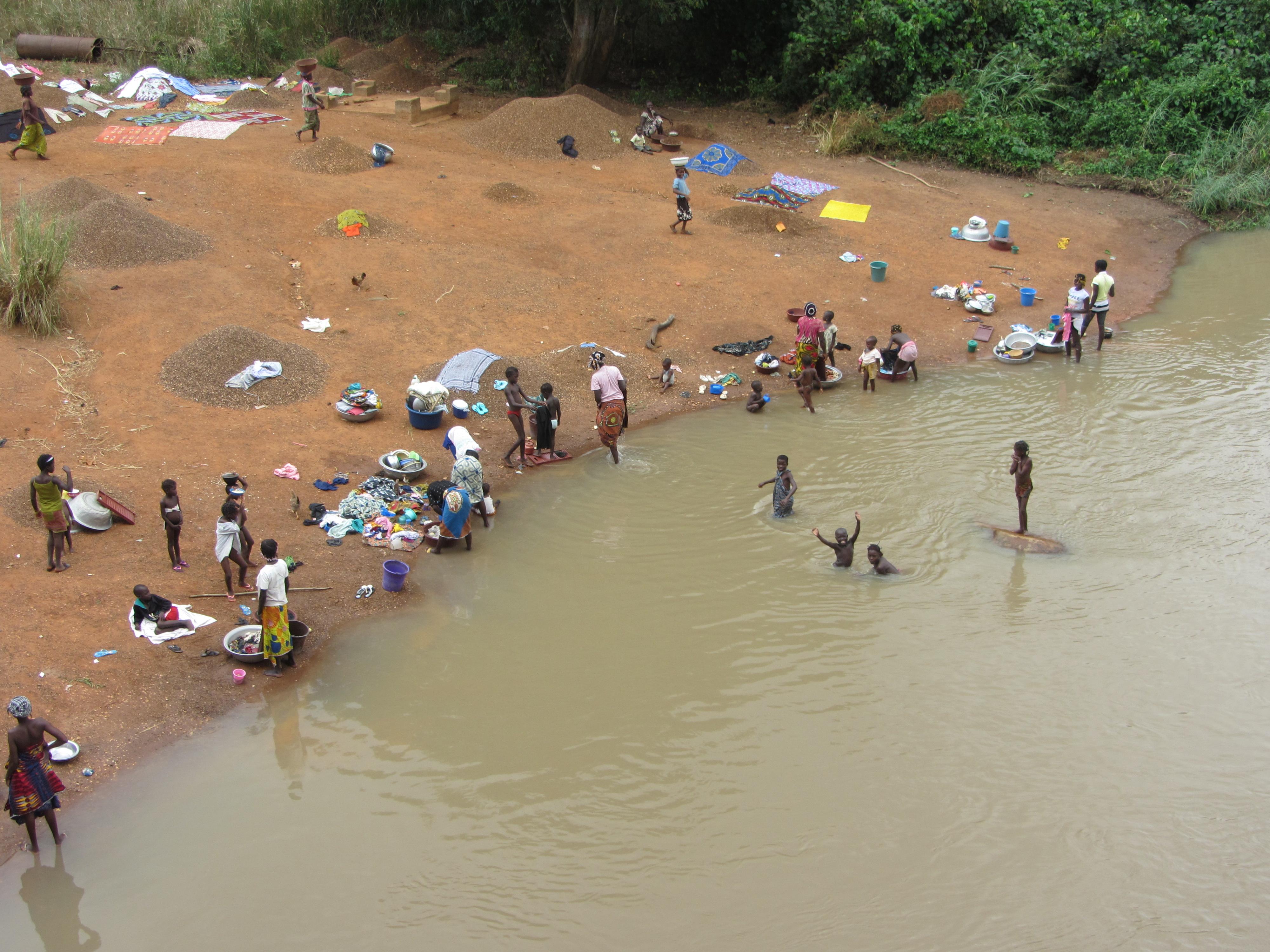 Mujeres y niños lavando y bañándose a la vera del río