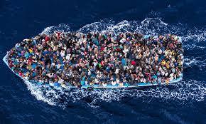 Una barcaza abarrotada de inmigrantes en aguas del Mediterráneo
