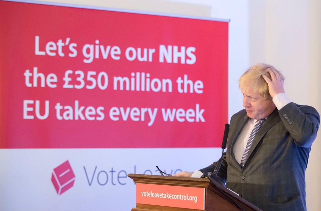 """Boris Johnson rascándose la cabeza ante un anuncio mentira que decía que """"demos a juestro Serivicio Nacional de Salud, los 350 millones de libras que entregamos a Europa cada semana"""
